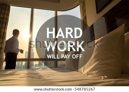 "Maid-up bed in cozy room. Young businessman with coffee cup standing at window looking at city scenery on the background. Motivational text ""Hard work will pay off"""