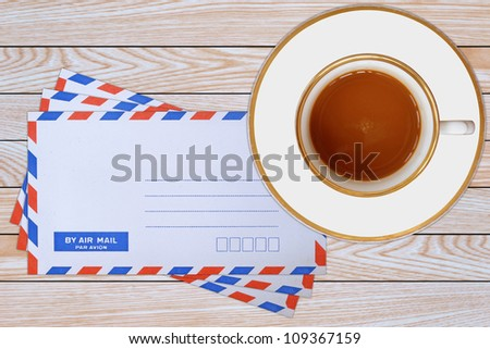 mail envelope and coffee cup on wooden background