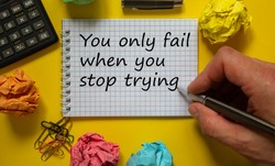 Mail hand writing 'You only fail when you stop trying' on white note, beautiful yellow background, colored paper clips, metalic pen, cap and calculator. Business concept.