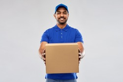 mail service and shipment concept - happy indian delivery man with parcel box in blue uniform over grey background