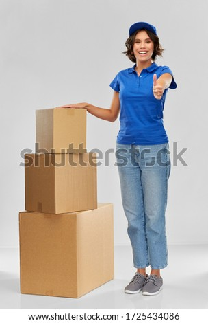 mail service and shipment concept - happy smiling delivery girl with parcel boxes in blue uniform over grey background Stock photo ©