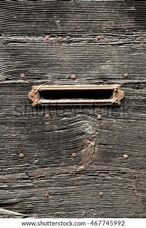 Mail slot in old wooden door closeup