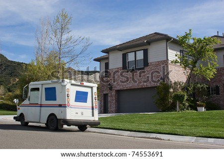 Mail truck makes a stop in a residential neighborhood.