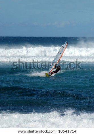 Mail windsurfer glides across the water ahead of the rolling waves.  Blue skies and water.