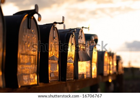 Mailboxes in row at sunset - stock photo
