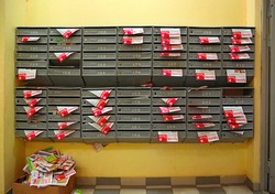 Mailboxes in the entrance hall of a residential house filled with paper flyers with the inscription in russian language Red and White. City Balashikha, Russia.