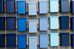 Mailboxes of varying blue color set in uneven rows.