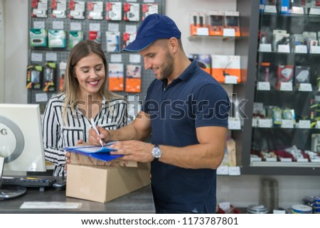 Mailmain delivering items to the girl inside the shop Photo stock ©
