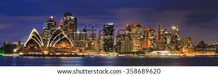 Main australian city Sydney at sunset across Harbour brightly illuminated. Cityscape landmarks including high-rise office towers and buildings around circular quay #358689620