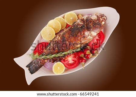 main course: whole fried sunfish on plate with lemons and peppers