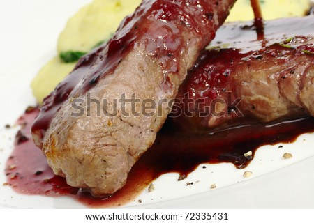 Main dish: Meat with red pepper sauce and mashed potato in the back (Selective Focus, Focus on the front of the left meat)
