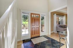 Main door entrance hallway with wooden door and natural stone dark tiles.