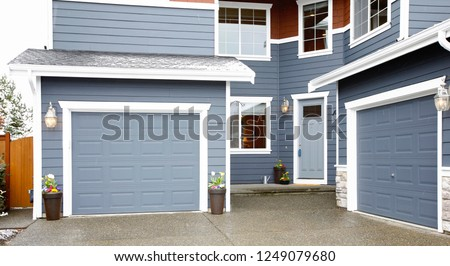 Main entrance of a grey two story tall house exterior. #1249079680
