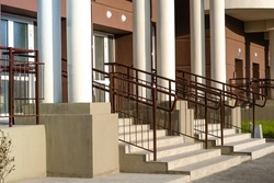 main entrance with stairs and railings of  residential apartment building with brown walls and white columns. Construction of new housing.