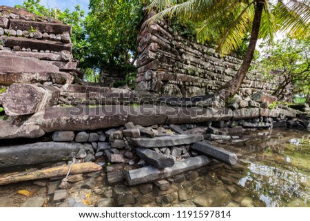 Main gates inside walls of Nan Madol - prehistoric ruined stone city built of basalt slabs on islands and canals, overgrown with palms. Pohnpei, Micronesia, Oceania