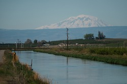 main irrigation canal for wapato irrigation project lower yakima valley washington with mt adams volcano in the distance