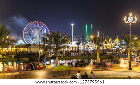 Main square and lake in Global Village with crowd and attractions  in Dubai, UAE. Brightly colouredl lights and highly detailed pavilion facades have helped make Global Village one of Dubai's mos Stock fotó ©
