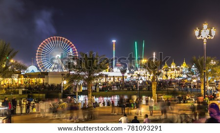 Main square and lake in Global Village with crowd and attractions timelapse in Dubai, UAE. Brightly colouredl lights and highly detailed pavilion facades have helped make Global Village one of Dubai's #781093291