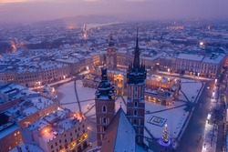 Main square Rynek of the Old Town of Krakow Poland in winter. St. Mary's Basilica Gothic church and Krakow Cloth Hall, covered in snow at evening with Christmas tree, decorations and lights.