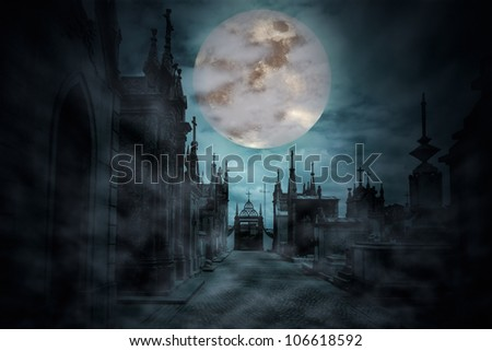 Main street of an old European cemetery in a cloudy and foggy full moon night