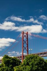 Main tower of 25th April bridge (Ponte 25 de Abril) Lisbon. Golden gate look alike bridge in Portugal. Tree and beautiful sky background. Vertical photo.