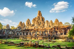 Main view of ancient Bayon temple in Angkor Thom in evening sun. Mysterious Angkor Thom nestled among rainforest in Siem Reap, Cambodia. Enigmatic Angkor Thom is a popular tourist attraction.