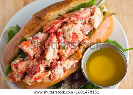 Maine Lobster Roll, traditional classic American Sandwich. New England classic, fresh Maine Lobster in homemade mayo with chives served in soft hero roll with crisp lettuce.