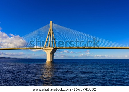 Mainstay of the Rion-Antirion Bridge in the light of the rising sun . Rion-Antirion Bridge connects the Peloponnese Peninsula with mainland Greece.