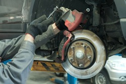 Maintenance and repair of cars in the service center. Close-up of the hands of a mechanic performing a brake pad replacement. Return of the brake pad cylinders by means of a depressor.