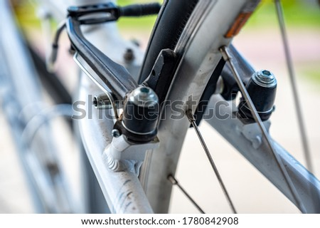 Photo of  Maintenance check of a peddle bike inspecting the brakes in the summer.