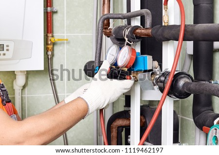 Maintenance engineer checking technical data of heating system equipment in a boiler room. Plumber installing pressure meter for house heating system. #1119462197