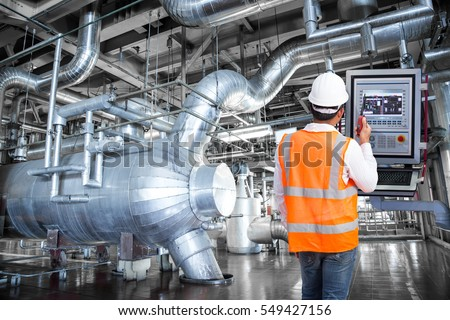 Maintenance engineer looking at monitor control in thermal power plant factory