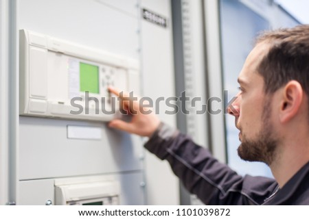 Maintenance engineer testing medium voltage switchgear and bay control unit. Relay protection system #1101039872