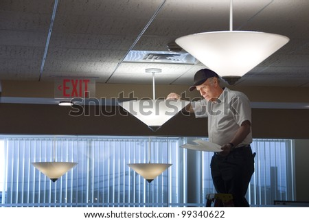 Maintenance man changing light bulbs in business office