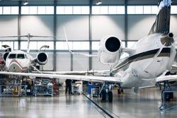Maintenance of airplane in large white hangar