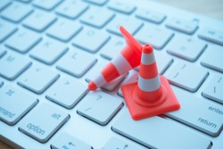 Maintenance, repair, under construction in computer system from virus or ransomware concept. Close up orange white traffic warning cones or pylon on keyboard computer background with copy space.
