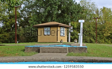Maintenance shed beyond the final 2 holes of a classic miniature golf course #1259583550