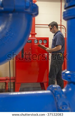 Maintenance worker checking on levels and condition of control panels