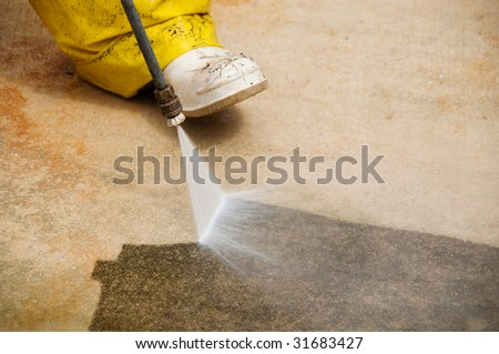 Maintenance worker cleaning old dirty driveway with a pressure cleaner