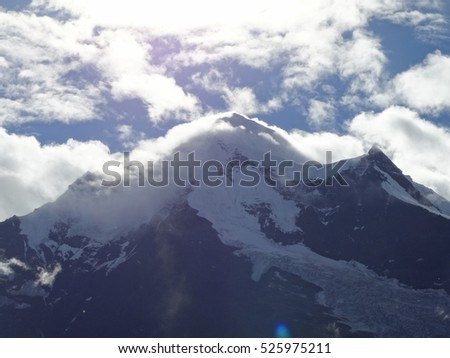 Majestic and pure Meili Snow mountain Peak in Yubeng Village in Yunnan Province, China, with clouds and sunshine beams, blue and white #525975211