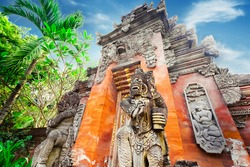 Majestic and tall rock statues Barong Lion Guard near shrine walls lit by sunshine at sunny day, Gunung Kawi Temple Complex, Bali, Indonesia. Balinese mythological creature, made of volcanic rock