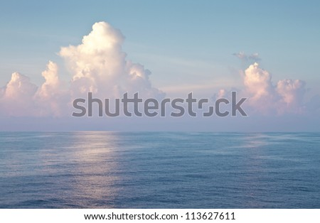 Majestic blue open sea and bright blue cloudy sky landscape with copy space.
