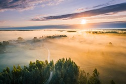 Majestic church covered in fog and surrounded by forest. Aerial view over picturesque countryside with at sunrise with long light rays.
