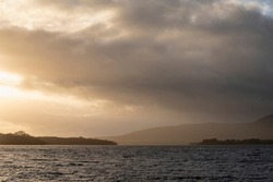 Majestic landscape image of Milarrochy Bay on Loch Lomond in Scottish Highlands with stunning Winter evening ligh