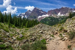 Majestic Maroon Bells peaks seen from the rugged Crater Lake Trail on a sunny day with blue sky in summer near Aspen, Colorado