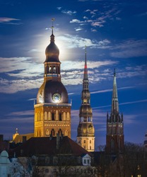 Majestic mediaval church towers of Riga in moonlight at night time. Dome cathedral and St. Peter's church backlit by the moon. Historical architecture of Riga.