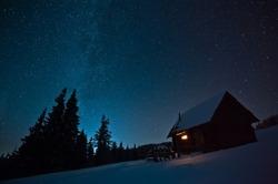 Majestic Milky Way over the winter mountains landscape. Night scene. Wooden house with light in window. Kukul ridge, Carpathians, Ukraine, Europe.