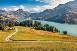 Majestic morning view of Roselend lake/Lac de Roselend. Picturesque autumn scene of Auvergne-Rhone-Alpes, France, Europe. Beauty of nature concept background. Amazing world of Alpine Mountains.
