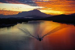 Majestic mount Kinabalu with fisherman in the boat go to sea,beautiful sunrise and amazing sky clouds at Mengkabong river, Tuaran,Sabah,Borneo.