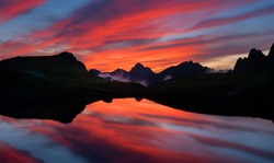 majestic mountain lasndscape at sunset with reflections over the lake